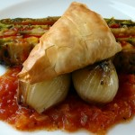 Spinach puff pastry with layers of zucchini, eggplant and peppers over grilled onions and tomato salsa